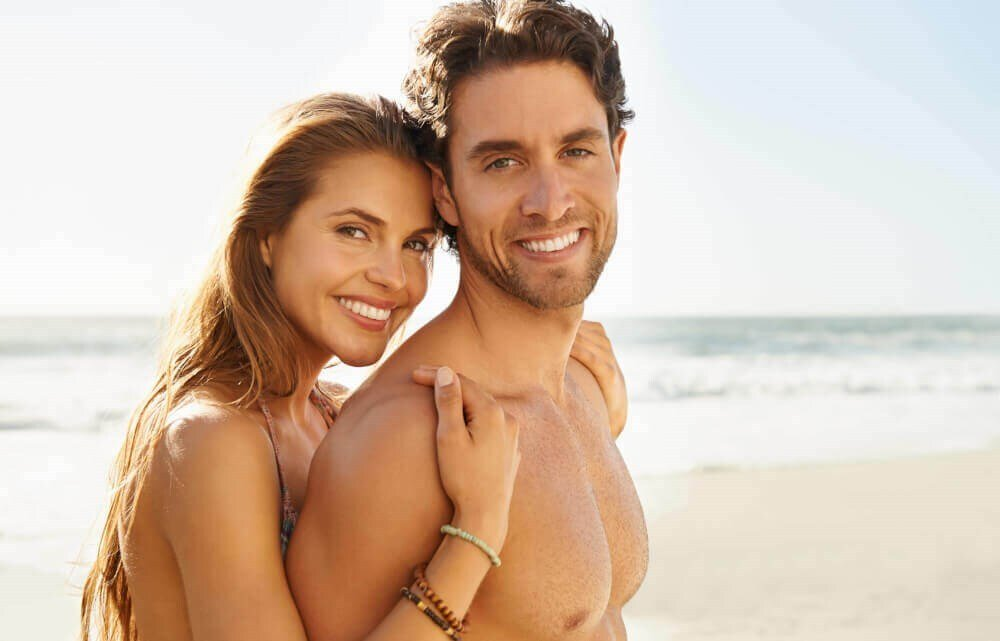 Male and Female Couple Smiling at the beach